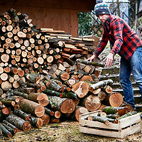 A photograph of a person collecting firewood from a log store outside a house in Savoie, France.
