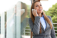 Happy businesswoman answering cell phone by glass door