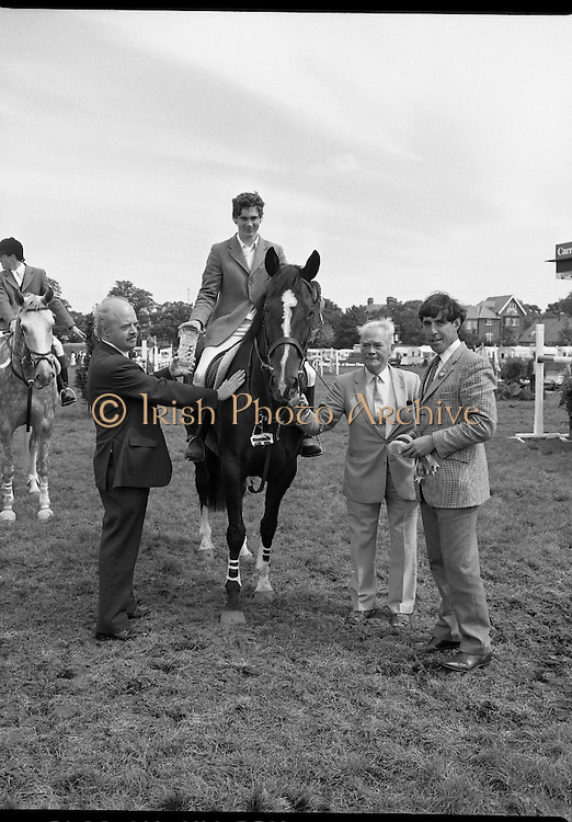 """Guinness Competitions At The RDS Horse Show.(R39)..1986..09.08.1986..08.09.1986..9th August 1986..At the Dublin Horse Show at the RDS, Guinness sponsor several events,The Guinness Match International, The Novice Championship and the Guinness Tankard...Photograph of Stephen Smyth aboard """"Hilton Nelly' winner of the Novice Championship being presented with his trophy by Mr Dick Frost,Guinness Group Sales, included in the picture is Mr Arthur Mallon, Monaghan ,owner of 'Hilton Nelly'. One of the judges of the event also presents the winners rosettes."""