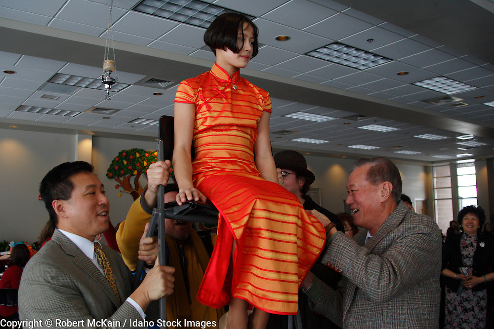 IDAHO. Boise. Asian Jewish girl lifted by her father and grandfather in chair for traditional Chair Dance at her Bat Mitzvah. December 2008. #pa080729 MR