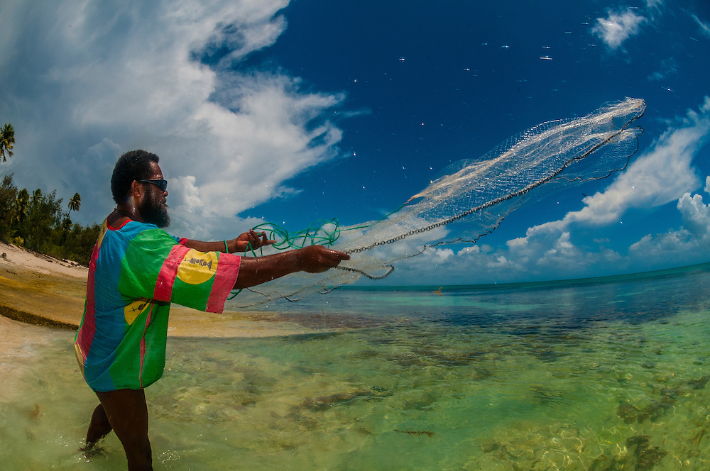 "Local Kanak (Melanesian) man casting a fishing net (in French ""Epervier"", hawk net), Mouli, Island of Ouvea, Loyalty Islands, New Caledonia"