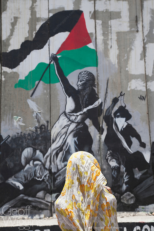 Woman gazes at graffiti covered Israeli West Bank Barrier, Bethlehem, Palestine Territory Occupied