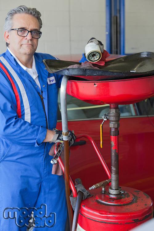 Portrait of senior mechanic standing besides car spray paint equipment