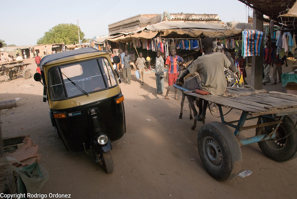 A rickshaw and a donkey-pulled kart drive across the streets of Abyei.