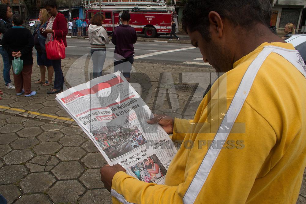 SAO PAULO 08 DE JULHO DE 2013 - Moradores da favela da Ilha que pegou fogo no complexo Heliopolis acompanham tarde desta segunda-feira (08), noticias publicada em jornal sobre o incendio. (Foto: Amauri Nehn/Brazil Photo Press)