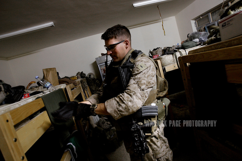 BASRA, IRAQ - JULY 4: 1st Lt. Phil Wagner, of USMC 1st Battalion 26th Brigade 2nd Division, from Ohio, prepares for an evening patrol in the poverty stricken neighborhood of Hayaniyah, July 4, 2008, Basra, Iraq. When British forces withdrew in 2007, Basra deteriorated into street battles between numerous Shiite militias and criminal gangs. In April 2008, Iraqi prime minister, Nouri al Maliki, sent two Iraqi army divisions to retake control of Basra. While the fighting has ended, unemployment is rife, at about 70 per cent. Since early 2008, Iraq's security situation has improved with oil production increasing, record government surplus and easing sectarian tensions. (Photo by Warrick Page)