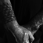 "The hands and tattoos of Billy Fields, a traditional craftsman who constructed hill for Hölua sledding as part of the the Makahiki season celebration held on the North Shore of Oahu. In the Hawaiian language, the word Makahiki means ""year"" as well as the change from harvest time to the beginning of the agricultural season. Hölua sledding is still practiced both on grassy hills, as well as down mountains made of volcanic rock."