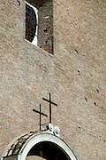 Detail of an ancient brick Roman Catholic church with a plain cross and copy space. Rome, Italy.