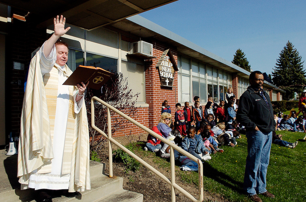 Fr. Dennis Witz, pastor of St. Philip Neri Parish in Milwaukee, recites a prayer during an Arbor Day tree-planting ceremony in front of St. Philip Neri School. Children planted several trees in observance of the annual event. (Photo by Sam Lucero)