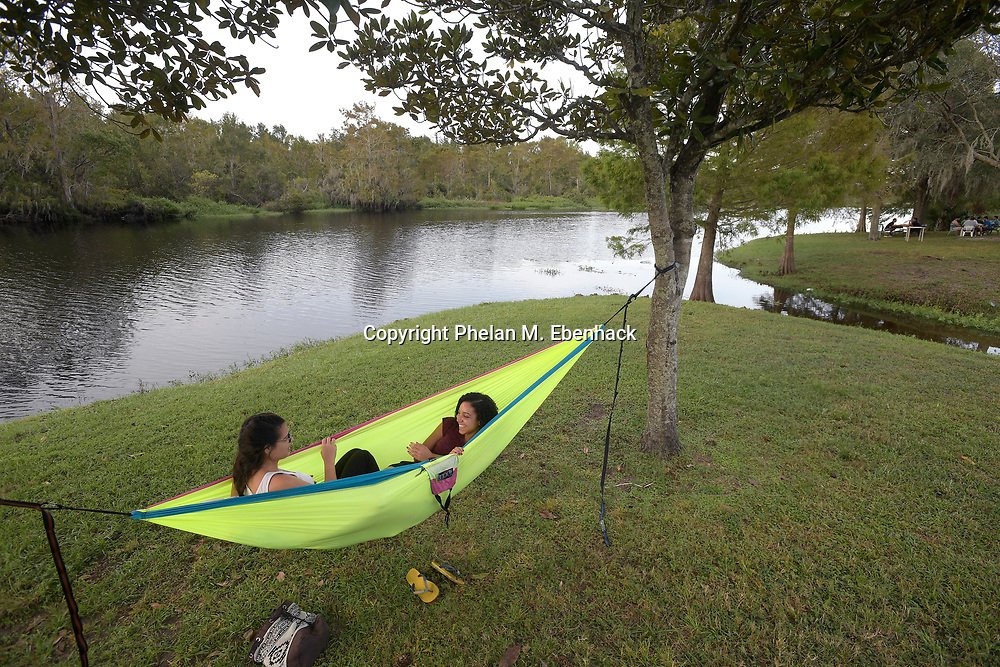 Stephanie Saez, left, and Tayla Mason relax in a hammock between two trees along a riverfront trail in Jay Blanchard Park Saturday, Oct. 21, 2017, in Orlando, Fla. (Photo by Phelan M. Ebenhack)
