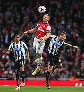 Lukas Podolski of Arsenal (centre) beats Mathieu Debuchy of Newcastle United in an aerial battle during the Barclays Premier League match at the Emirates Stadium, London<br /> Picture by David Horn/Focus Images Ltd +44 7545 970036<br /> 28/04/2014