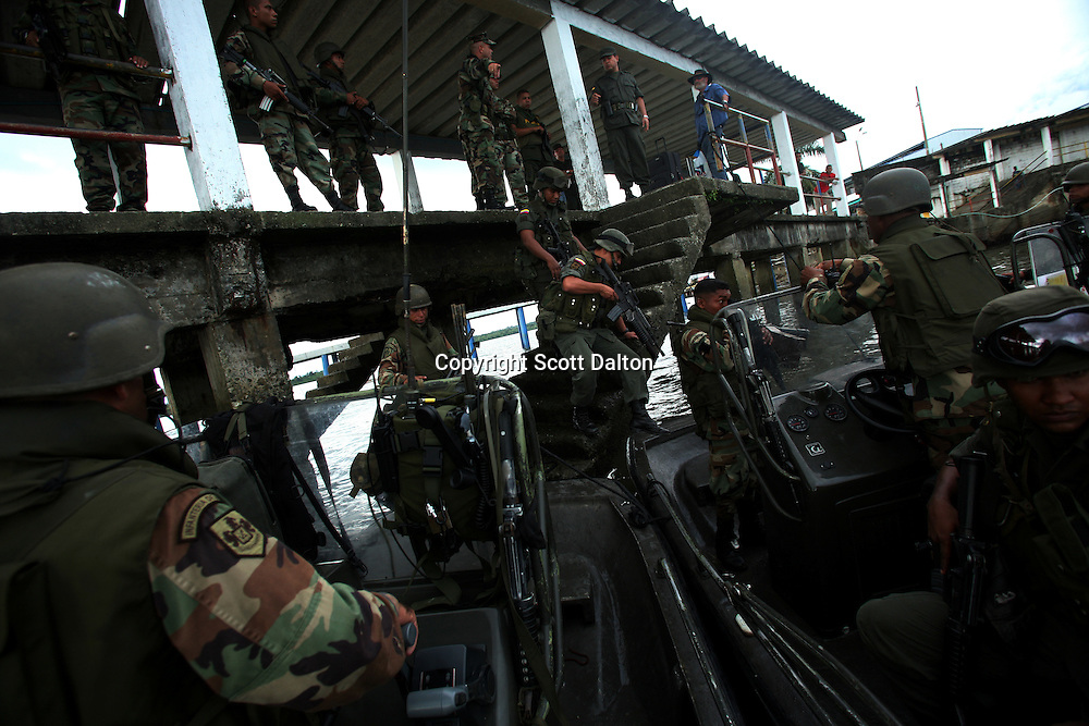 Members of the Colombian Navy board boats to patrol the waters along the coast that are used to ship drugs in Buenaventura, on the Pacific Coast of Colombia, on Monday, May 14, 2007. Buenaventura is in the midst of a spree of violence over control of drug shipments from the poor barrios in the city. Many of the neighborhoods have a strong presence of FARC militias that control most of the drug trade in the city. (Photo/Scott Dalton)