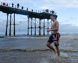 © Licensed to London News Pictures. <br /> 01/01/2017. <br /> Saltburn by the Sea, UK.  <br /> <br /> A man walks from the cold waters of the North sea as he takes part in the annual New Year Day dip at Saltburn beach.<br /> <br /> The event helps to raise money for the Saltburn Animal Rescue Association.<br /> <br /> Photo credit: Ian Forsyth/LNP