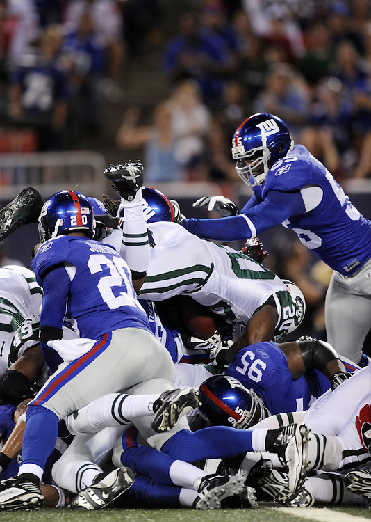 EAST RUTHERFORD, NJ - AUGUST 29: Thomas Jones #20 of the New York Jets attempts to dive over the pile during the preseason game against the New York Giants at Giants Stadium on August 29, 2009 in East Rutherford, New Jersey. The New York Jets beat the New York Giants 27-25. (Photo by Rob Tringali) *** Local Caption *** Thomas Jones