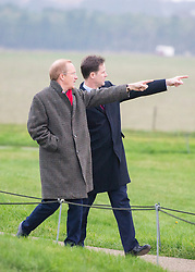© Licensed to London News Pictures. 01/12/2014. Wiltshire, UK Simon Thurley (red scarf) Director of English Heritage tours the site with Nick Clegg. British Prime Minister Nick Clegg visits The World Heritage Site of Stonehenge in Wiltshire today 1st December 2014. A tunnel passing Stonehenge is among dozens of new road schemes announced by the government, as part of £15bn of improvements to England's roads.. Photo credit : Stephen Simpson/LNP
