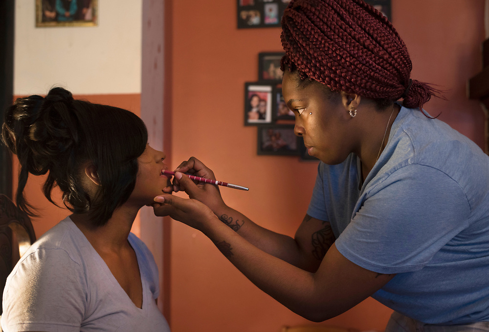 Michelle White (right) applies lip liner to Tyneisha Wilder during preparations East Allegheny High School's prom at Tyneisha's foster home in Wilkinsburg.
