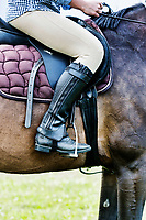 Close up photo of mature woman riding horse in ranch