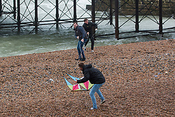 © Licensed to London News Pictures. 14/11/2015. Brighton, UK. Brighton beach is battered by strong winds and powerful waves. A group of friends play with kites on the beach. Today November 14th 2015. Photo credit : Hugo Michiels/LNP