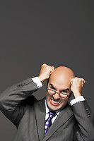 Bald businessman fists on head pounding head making a face