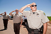 04 AUGUST 2010 -- GILBERT, AZ: Mariciopa County Deputy Hanse (CQ HANSE), Detention Officer Horton (CQ) and Detention Officer London (CQ) LEFT TO RIGHT, BACKGROUND TO FOREGROUND, salute as Det. Carlos Ledesma's cortege passes at the funeral for Chandler police detective Carlos Ledesma Wednesday. They are members of the azhighwayofheroes.com organization, which honors fallen first responders. Ledesma was killed during a shoot out with suspected drug dealers during an undercover operation in south Phoenix Wednesday July 28.  PHOTO BY JACK KURTZ   THEY SAID LAST NAMES ONLY