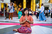 15 JUNE 2013 - YANGON, MYANMAR: A woman prays at Shwedagon Pagoda. Shwedagon Pagoda is officially known as Shwedagon Zedi Daw and is also called the Great Dagon Pagoda or the Golden Pagoda. It is a 99 meter (325 ft) tall pagoda and stupa located in Yangon, Burma. The pagoda lies to the west of on Singuttara Hill, and dominates the skyline of the city. It is the most sacred Buddhist pagoda in Myanmar and contains relics of the past four Buddhas enshrined: the staff of Kakusandha, the water filter of Koṇāgamana, a piece of the robe of Kassapa and eight strands of hair from Gautama, the historical Buddha. Burmese believe the pagoda was established as early ca 540BC, but archaeological suggests it was built between the 6th and 10th centuries. The pagoda has been renovated numerous times through the centuries. Millions of Burmese and tens of thousands of tourists visit the pagoda every year, which is the most visited site in Yangon. PHOTO BY JACK KURTZ