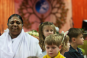 Voor de darshan mediteert Amma, omringd door kinderen. In de Expo in Houten is Mata Amritanandamayi, beter bekend als Amma of 'hugging mother', aanwezig om mensen te omhelzen en te inspireren. Het driedaags benefiet in Houten is het grootste spirituele festival in Nederland en zal naar verwachting 15.000 bezoekers trekken.<br /> <br /> Before she starts with the darshan Amma is meditating, surrounded by children. In the Expo in Houten people are gathering to get a darshan, or hug, by  Mata Amritanandamayi, also known as Amma or 'hugging mother'. Amma is travelling through the world to hug people for inspiring them to make a better world. Amma is one of the twelve most influence spiritual leaders of the world. The event in Houten lasts for three days and is the biggest spiritual event of The Netherlands.