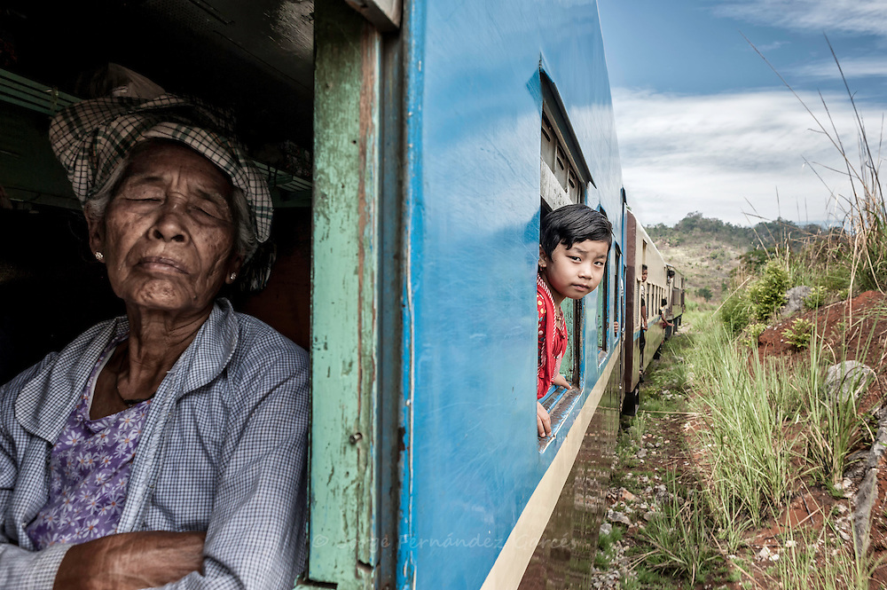 Girl looking out the window of a slow train and old woman sleeping, Myanmar, Asia
