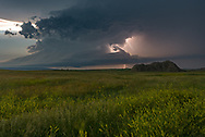A warm and humid wind gusted across the prairie causing the grasses and goldenrods to sway back and forth. In the distance a supercell thunderstorm spun away furiously. I knew a tornado was on the ground in Montana, but I couldn't see it until it crossed into South Dakota and emerged from behind a distant hill. The first tornado roped out after a couple minutes, but then this funnel quickly formed. It danced around, touching the ground briefly but not doing much. This was a cyclic supercell, which means it produced multiple tornadoes. As one ropes out, the wall cloud regenerates and another forms. Tornado #3 would be a much more substantial wedge that stayed on the ground for about 20 minutes. After I saw the storm's movement, I knew I could move a bit closer to get a clearer view. Sunset was minutes away and there was not much time left before it got too dark to see.