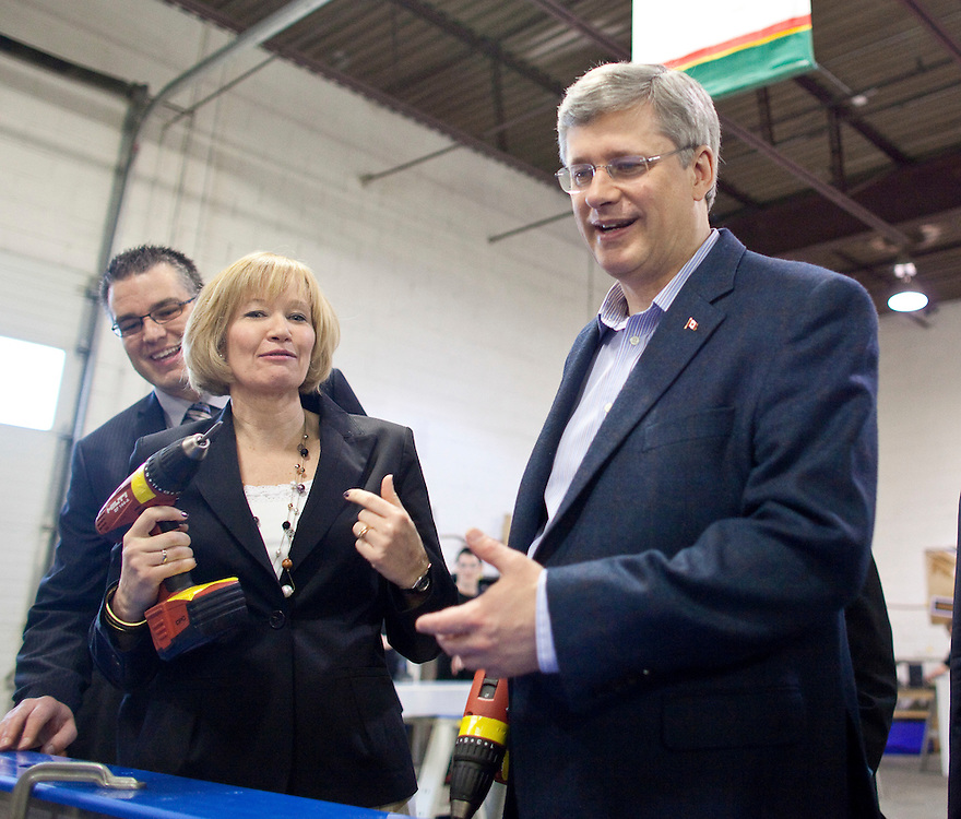Conservative leader Stephen Harper tries to explain after his wife Laureen told the media that Harper once bought her a drill as a gift during a campaign stop at hockey boards marker Sport Systems Unlimited in Waterloo, Ontario, April 27, 2011. <br /> AFP/GEOFF ROBINS/STR