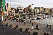 Local people walking by the port of Gijon, Asturias, Northern Spain. A paseo.