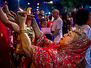 19 OCTOBER 2018 - BANGKOK, THAILAND: A woman dances with fire during Navratri observances in Bangkok. Navratri is a nine night (10 day) long Hindu celebration that marks the end of the monsoon and honors of the divine feminine Devi (Durga). The festival is celebrated differently in different parts of India, but the common theme is the battle and victory of Good over Evil based on a regionally famous epic or legend such as the Ramayana or the Devi Mahatmya. Navratri is celebrated throughout Southeast Asia in communities that have a large Hindu population. Because Navratri honors the feminine Devi, Navratri is especially popular with Thai women and transgendered people.  PHOTO BY JACK KURTZ