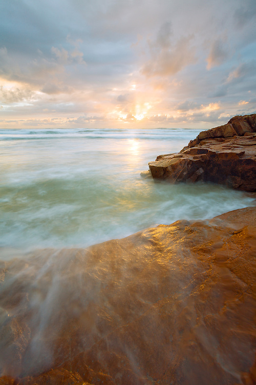 The first moments of sunlight add the golden touch to the foreshore rocks.