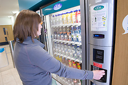 Woman buying a drink from the chilled vending machine at her sports leisure centre,
