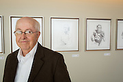 Bart Forbes poses for a portrait in front of a series of sketches of iconic San Francisco 49ers, including Leo Nomellini, Joe Montana, and Dwight Clark, during the Levi's Stadium Art Collection grand opening event at Levi's Stadium in Santa Clara, California, on August 1, 2014. (Stan Olszewski/SOSKIphoto for Content Magazine)
