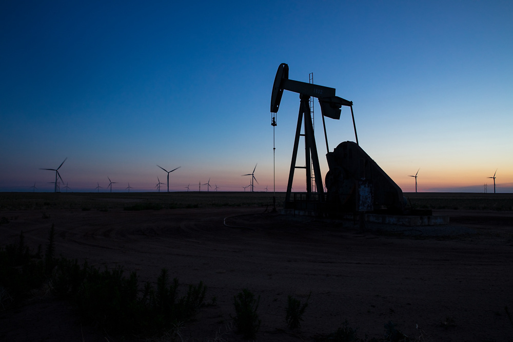 Pump jack with wind farm turbines on horizon silhouetted at sunset.