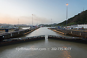 The Miraflores locks close behind a shiping vessel as it transits the Panama Canal at sunset.