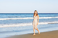 Young woman in summer dress walking along beach