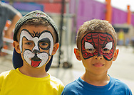 Brooklyn, New York, USA. 10th August 2013. GABRIEL RODRIGUEZ, with puppy face, and ELI RODRIGUEZ, with Spiderman Face, are 4 year old twin brothers from Manhattan, who had their faces painted by a volunteer artist Laura, during the 3rd Annual Coney Island History Day celebration.