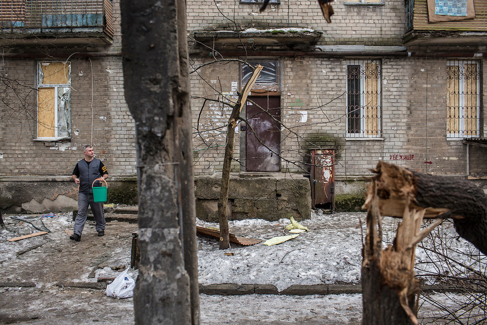 DONETSK, UKRAINE - JANUARY 23, 2015: A man outside an apartment building which was damaged by a rocket that landed nearby and exploded two days earlier in Donetsk, Ukraine. After the rebels finally took control of the heavily contested airport in Donetsk from the Ukrainian Army, they have promised an offensive to extend their territory further. CREDIT: Brendan Hoffman for The New York Times