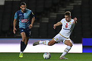 Milton Keynes Dons defender Callum Brittain (25) takes a shot at goal under pressure from Wycombe Wanderers midfielder Nick Freeman (22) during the EFL Trophy match between Milton Keynes Dons and Wycombe Wanderers at stadium:mk, Milton Keynes, England on 12 November 2019.