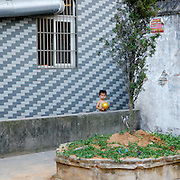 Young boy holding a golden ball looks out to the street from a courtyard.
