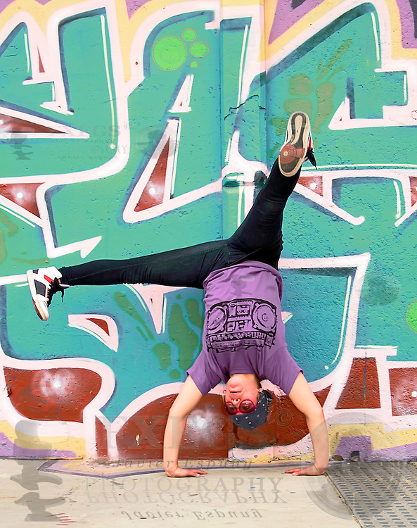Hip-hop breakdancer handsatnding with a graffited wall as background
