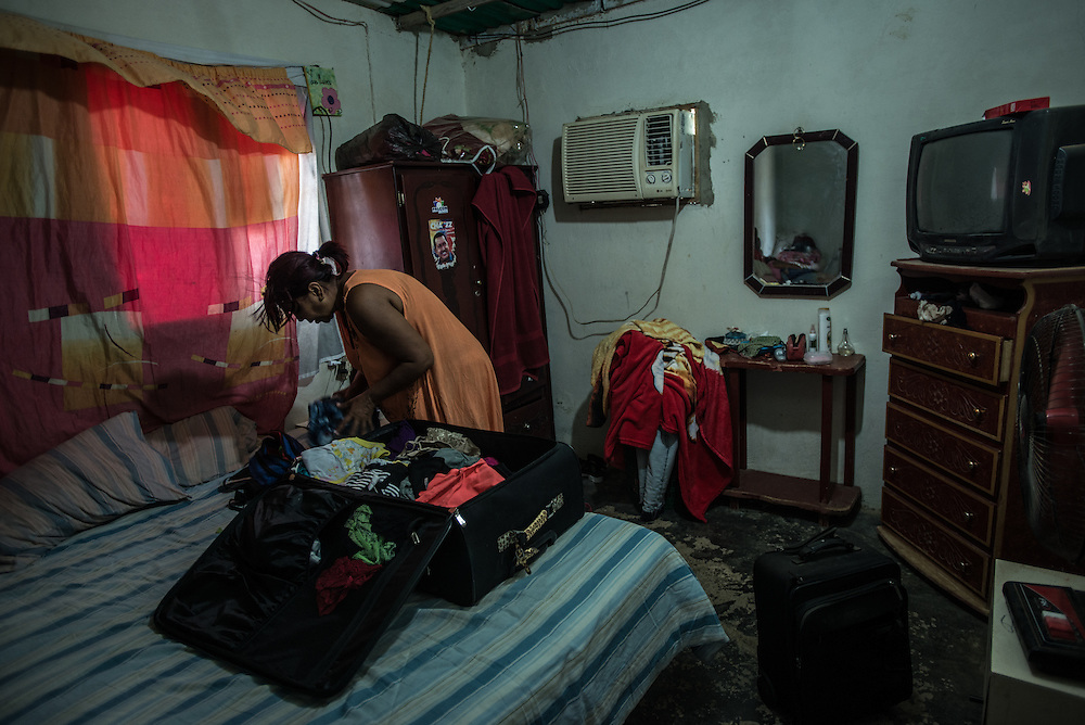 "LA VELA, VENEZUELA - SEPTEMBER 18, 2016: Maria Piñero chooses items from a large suitcase to pack into a much smaller bag of clothes and personal items. To escape the economic crisis in Venezuela, Ms. Piñero spent all of her savings to pay smugglers to take her in a small fishing boat to Curacao island. Smugglers tell migrants to barely bring anything with them, because they will have to swim to shore - and to be ready to leave at any minute, but made them wait for weeks, delaying the departure date over 8 times.  ""I'm nervous,"" said Maria. ""I'm leaving with nothing. But I have to do this. Otherwise, we will just die here hungry."" Well over 150,000 Venezuelans have fled the country in the last year alone, the highest in more than a decade, according to scholars studying the exodus. PHOTO: Meridith Kohut for The New York Times"