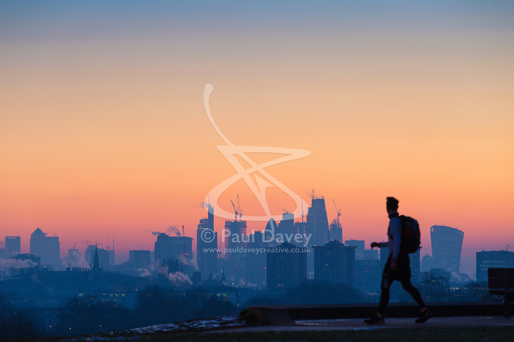 London, December 12 2017. A walker is in silhouette against the skyline before the sun rises on a clear very cold morning in London, seen from Primrose Hill in Camden. © Paul Davey