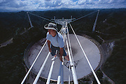 Orlando Rodriguez has worked at the Arecibo Observatory for over twenty years. He is seen here standing on the cables that suspend the Gregorian Platform.