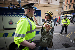 © Licensed to London News Pictures . 04/10/2015 . Manchester , UK . A policeman and a protester scuffle outside the conference venue . A demonstration against the Conservative government , organised by The People's Assembly , at Castlefield Bowl in Manchester , during the first day of the Conservative Party Conference in Manchester . Photo credit: Joel Goodman/LNP