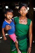 Pramila Tharu, 15, carries her 2 year old daughter Prapti in Bhaishahi village, Bardia, Western Nepal, on 29th June 2012. Pramila eloped and married at 12 and gave birth to Prapti at age 13. She delivered prematurely on the way to the hospital in an ox cart and her baby weighed only 1.5kg at birth. In Bardia, StC works with the district health office to build the capacity of female community health workers who are on the frontline of health service provision like ante-natal and post-natal care, especially in rural areas. Photo by Suzanne Lee for Save The Children UK