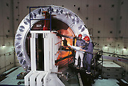 Physics: Stanford Linear Accelerator Center (SLAC). Rafe Schindler and Iris Abt with detector insert. Stanford Linear Collider (SLC) experiment, Menlo Park, California. With a length of 3km, the Stanford Linear Accelerator is the largest of its kind in the world. The accelerator is used to produce streams of electrons and positrons, which collide at a combined energy of 100 GeV (Giga electron Volts). This massive energy is sufficient to produce Z-zero particles in the collision. The Z-zero is one of the mediators of the weak nuclear force, the force behind radioactive decay, and was first discovered at CERN, Geneva, in 1983. The first Z-zero at SLC was produced on 11 April 1989. [1988]