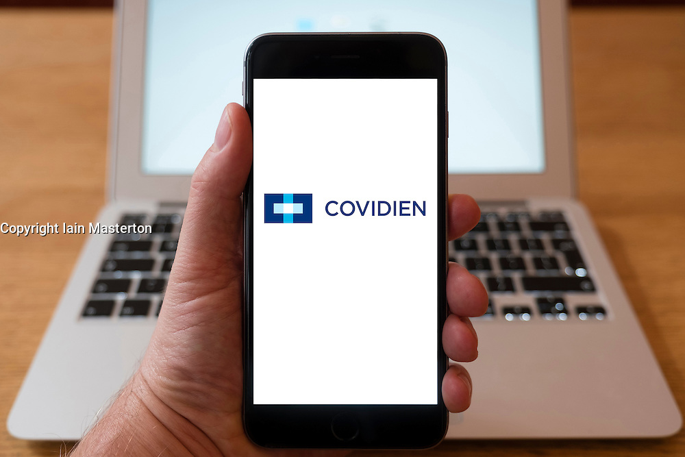 Using iPhone smartphone to display logo of Covidien, global health care products company