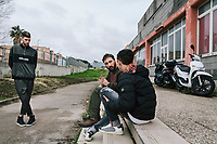 """NAPLES, ITALY - 16 MARCH 2018: Founder and President of """"Il Tappeto di Iqbal"""" Giovanni Savino (38, center) talks to a teenager who missed school and a potential school-dropout, while  Vice-President Marco Riccio (25, left) listens to the conversation, here at """"Il Tappeto di Iqbal"""" (Iqbal's carpet), a non-profit cooperative in Barra, the estern district of Naples, Italy, on March 16th 2018.<br /> <br /> Il Tappeto di Iqbal (Iqbal's Carpet) is a non-profit cooperative founded in 2015 and Save The Children partner since 2015 that operates in the Naple's eastern neighborhood of Barra children in the arts of circus, theater and parkour. It was named after Iqbal Masih, a Pakistani boy who escaped from life as a child slave and became an activist against bonded labor in the 1990s.<br /> Barra, which is home to some 45,000 people, has the highest rate of school dropouts in the Italian region of Campania. Once a thriving industrial community, many of the factories were destroyed in a 1980 earthquake and never rebuilt. The resulting de-industrialization turned Barra into a poor, decaying neighborhood. There are no cinemas, theaters, parks or public spaces in Barra.<br /> The vast majority of children from poor families are faced with the choice of working in the black economy or joining the ranks of the organised crime.<br /> Recently, Save the Children Italy opened a number of educational and social spaces in Barra. The centers, known as Punti Luce, or points of light, aim to help local kids stay out of the ranks of the organised crime and have also become hubs for Iqbal's Carpet to work."""